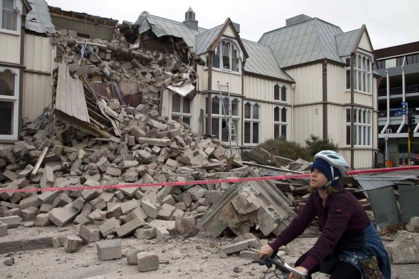 A cyclist rides past a damaged building in central Christchurch